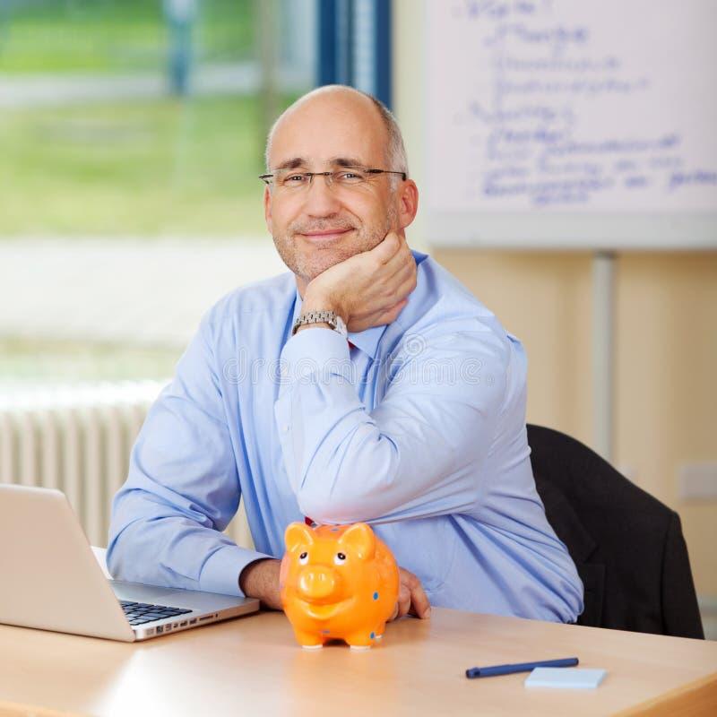 De glimlachende Bank van Zakenmanleaning on piggy stock fotografie