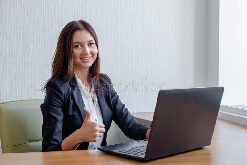 De glimlachende bedrijfs aan laptop werken en vrouw die beduimelt omhoog stoppen stock afbeeldingen