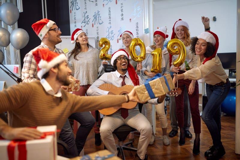 De glimlachende bedrijfsarbeiders hebben pret en het dansen in Kerstmanhoed bij van de Kerstmispartij en uitwisseling giften stock fotografie
