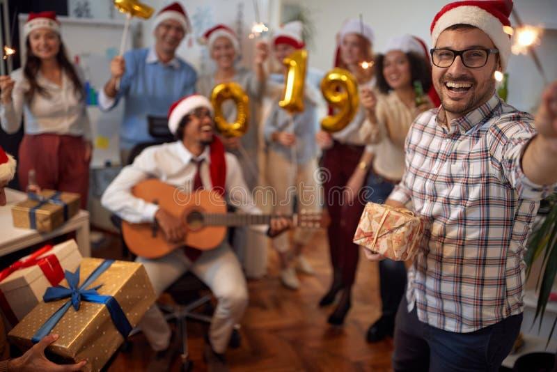 De glimlachende bedrijfsmens heeft pret in Kerstmanhoed bij Kerstmispartij met zijn collega's stock fotografie