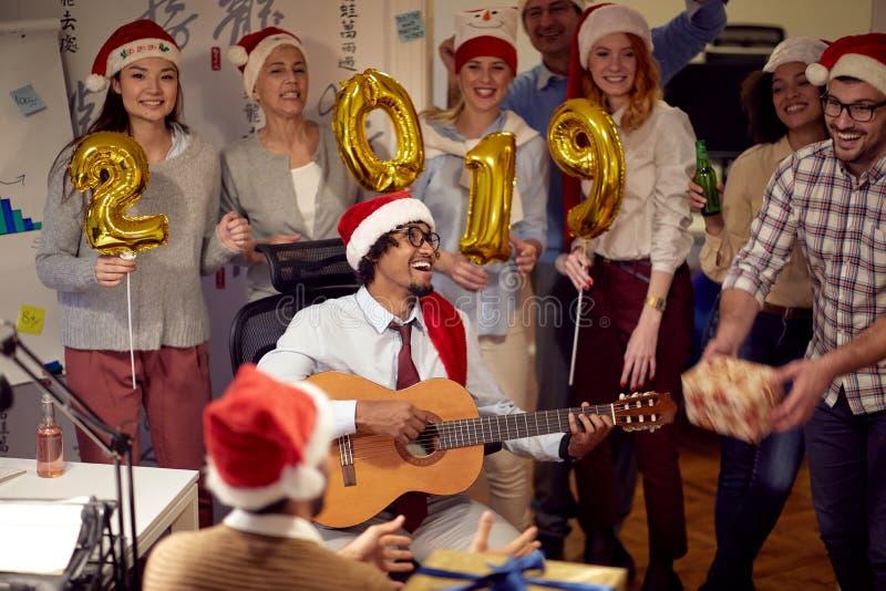 De glimlachende bedrijfsmensen hebben pret en het dansen in Kerstmanhoed bij Kerstmispartij stock foto's