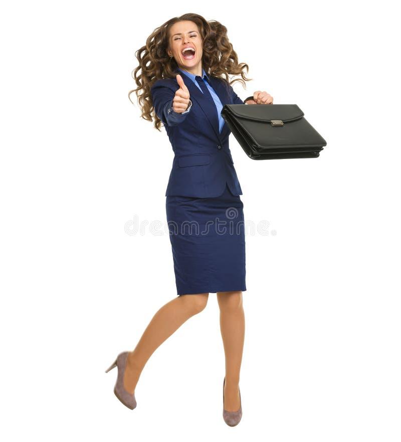 De glimlachende bedrijfsvrouw met en aktentas die beduimelt omhoog springen tonen stock afbeelding