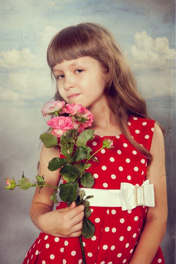 De glimlachende bloemen van de meisjeholding stock afbeelding