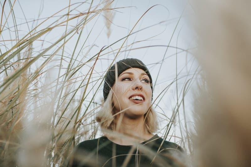 De glimlachende blondevrouw met breit hoed op omringd van rietinstallaties in aard stock afbeelding
