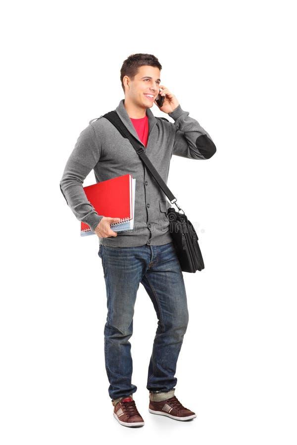 De glimlachende boeken van de jongensholding en het spreken op een telefoon stock afbeeldingen