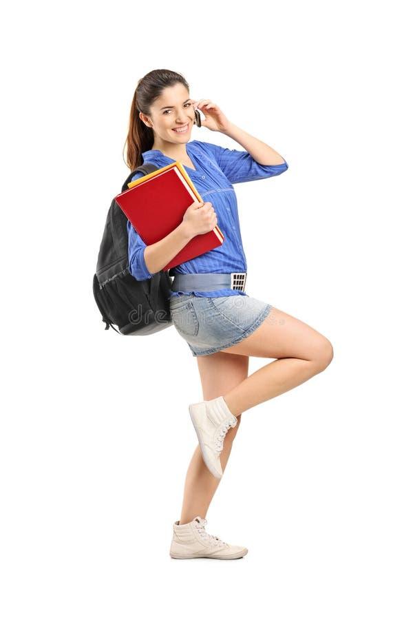 De glimlachende boeken van de meisjesholding en het spreken op een telefoon stock afbeelding