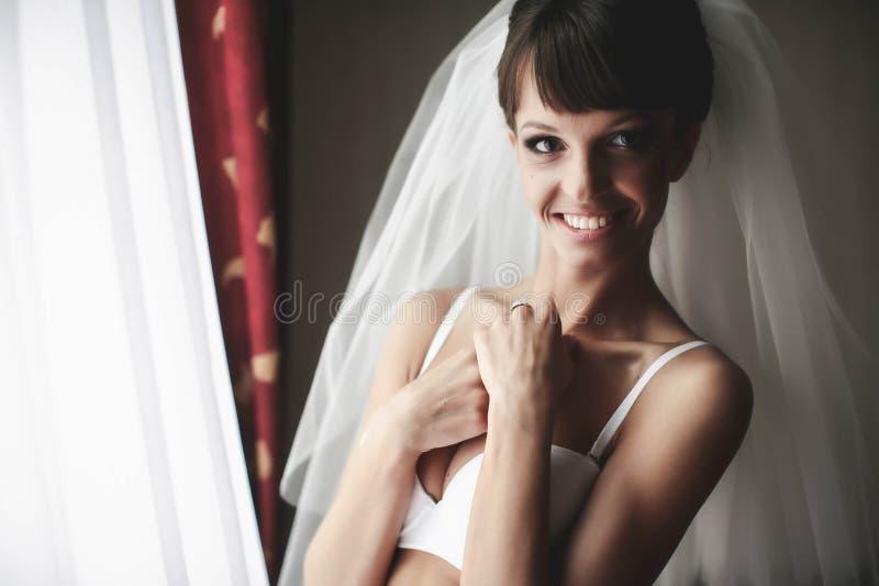 De glimlachende bruid stelt in bleekheid op de achtergrondgordijnen royalty-vrije stock afbeeldingen