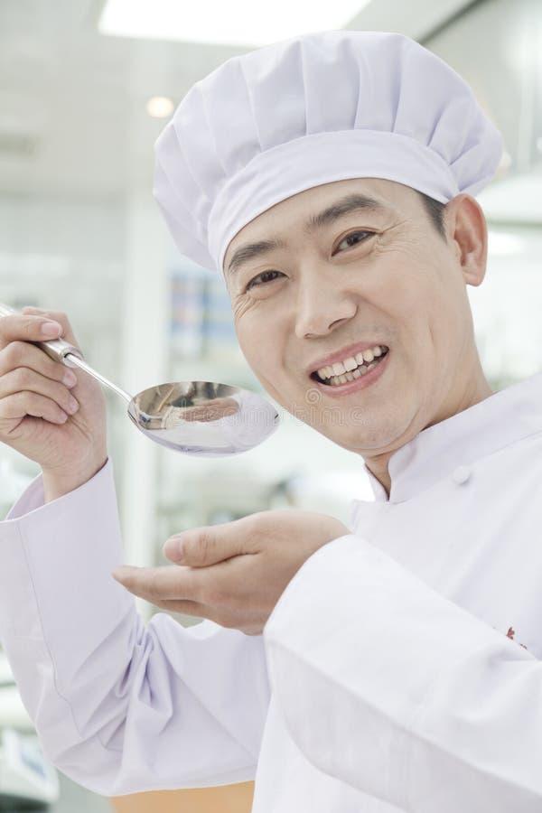 De glimlachende chef-kok met lepel hief aan zijn mond, proevend voedsel, portret op stock fotografie