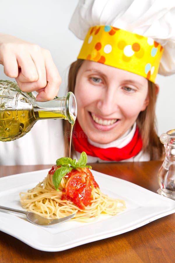 De glimlachende chef-kok versiert een Italiaanse deegwarenschotel royalty-vrije stock afbeeldingen