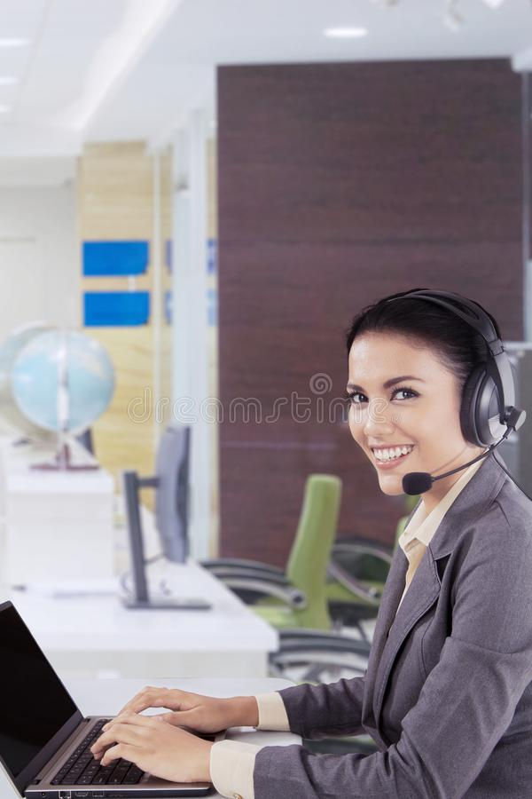 De glimlachende dame van de klantendienst met hoofdtelefoon stock afbeelding