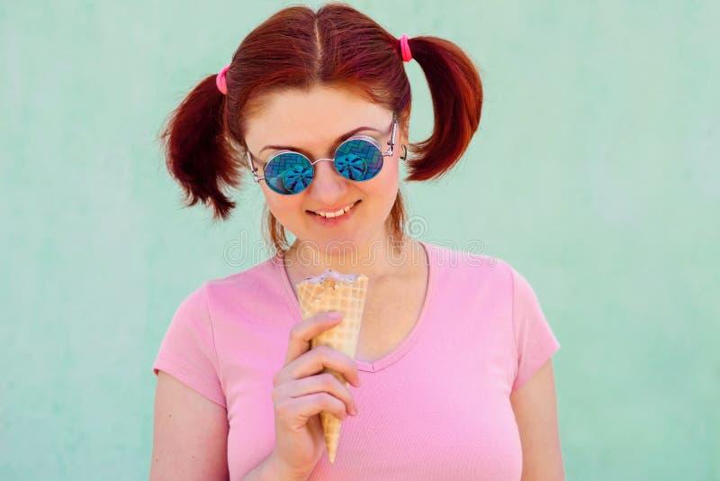 De glimlachende dappere jonge vrouw met vlechtenkapsel houdt roomijs in wafelkegel, denkt het in haar zonnebril na Stedelijke sti stock foto's