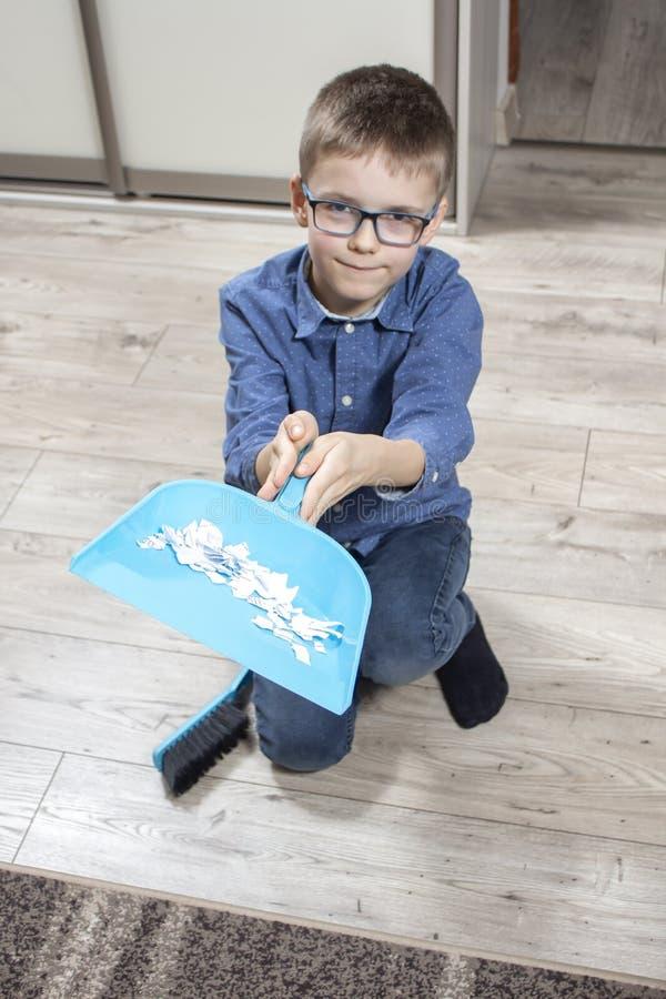 De glimlachende die jongen met glazen knielt op de vloer en houdt een lepel met documenten wordt gevuld stock foto's