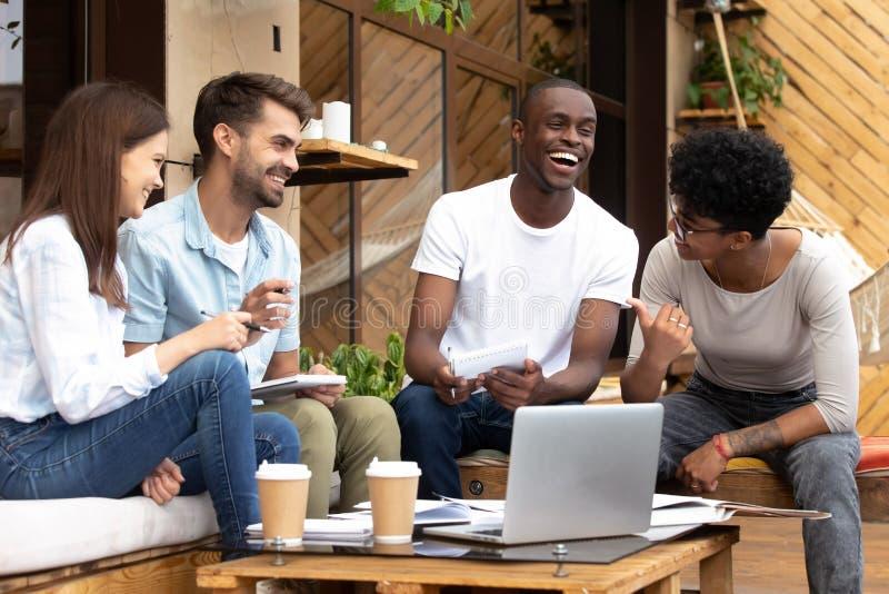 De glimlachende diverse millennial vrienden hebben pret bestuderend in koffie stock foto's
