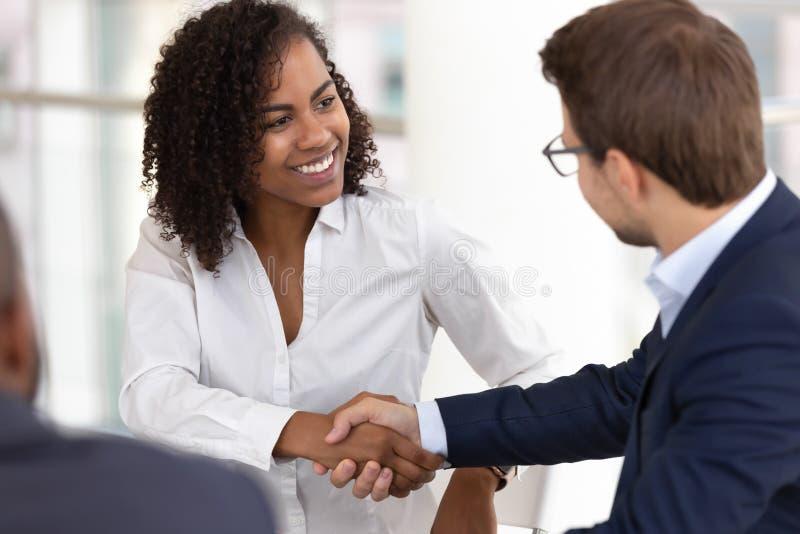 De glimlachende diverse onderneemster en zakenmanhanddruk maakt overeenkomst op vergadering royalty-vrije stock foto