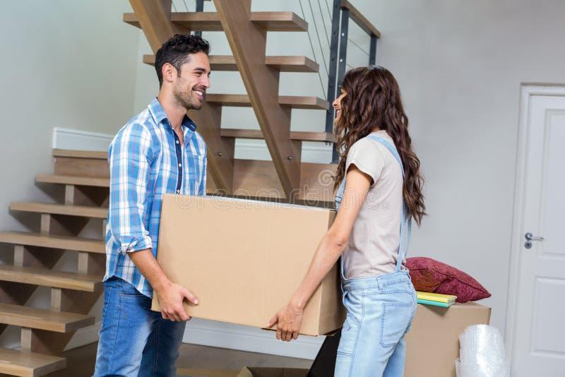 De glimlachende doos van het paar dragende karton stock fotografie