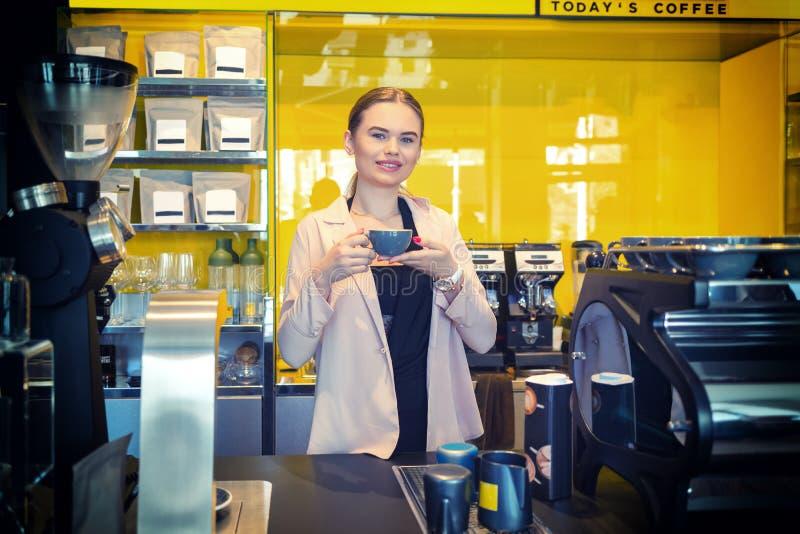 De glimlachende eigenaar die van de Koffiewinkel zich achter teller met kop van koffie bevinden stock afbeelding