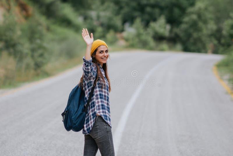 De glimlachende en golvende hand van de reizigersvrouw op de weg, de zomervakantie het reizen royalty-vrije stock afbeeldingen