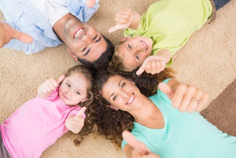 De glimlachende familie die op de deken in cirkel het tonen liggen beduimelt omhoog stock foto