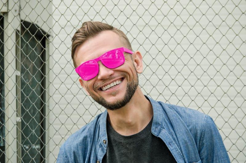 De glimlachende gebaarde jonge mens in roze zonnebril en denimoverhemd bevindt zich tegen de achtergrond van ketting-verbinding e royalty-vrije stock fotografie