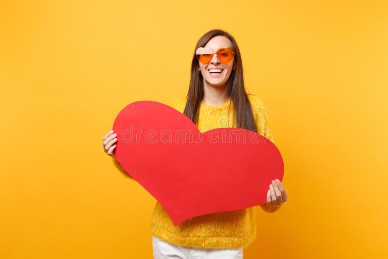 De glimlachende gelukkige jonge vrouw die in bontsweater en oranje hartoogglazen leeg leeg rood hart houden isoleerde op helder stock afbeeldingen