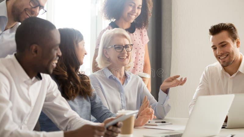 De glimlachende gelukkige multiculturele collega's die van bureauwerknemers samen lachen stock afbeelding