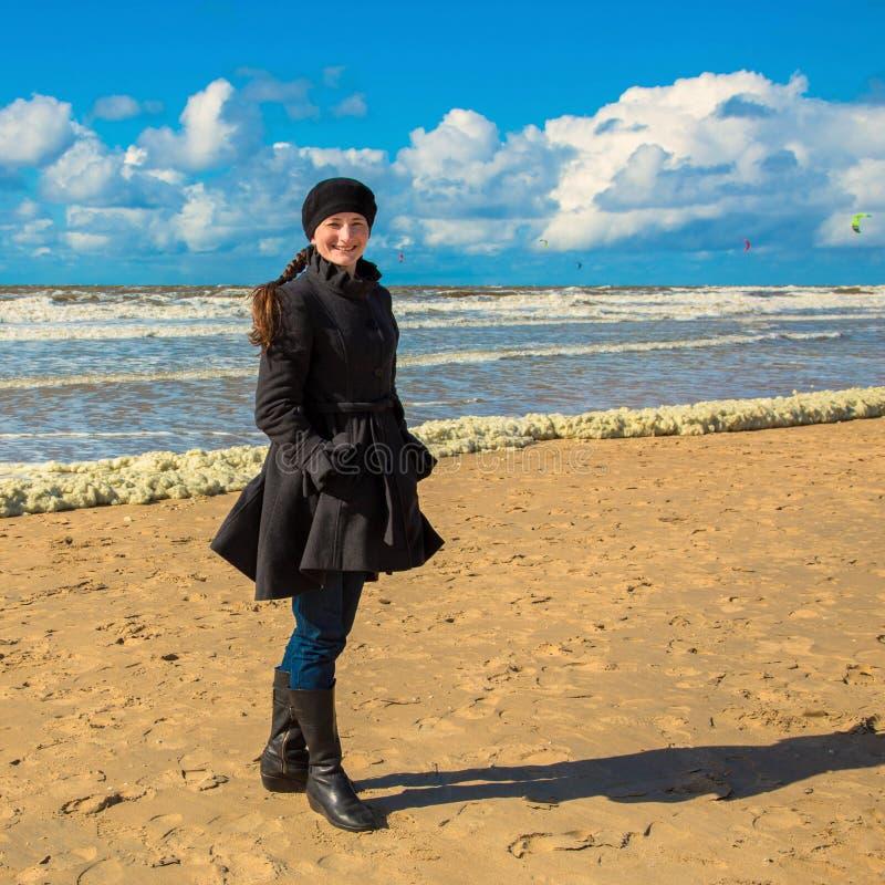 De glimlachende gelukkige vrouw kleedde zich in een laag bij het strand stock foto's