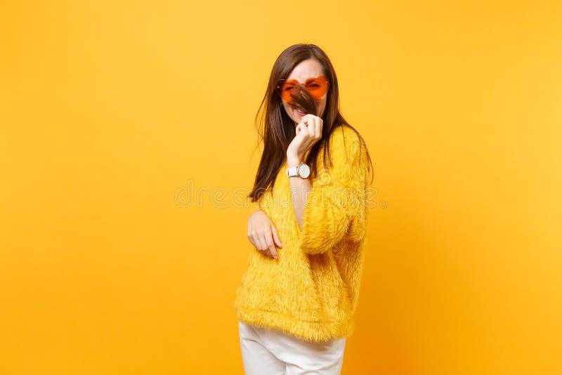 De glimlachende grappige jonge vrouw in van het bontsweater en hart het oranje glazen houden, die gezicht behandelen met haar iso royalty-vrije stock foto