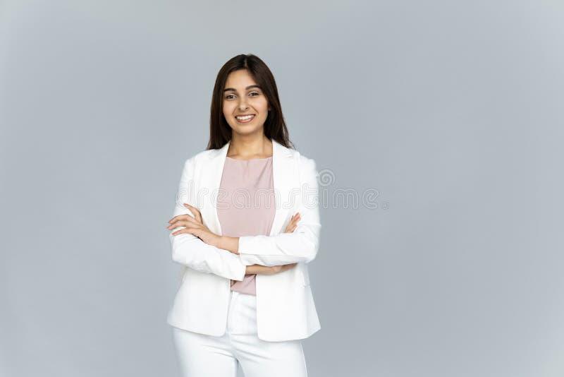 De glimlachende Indische die onderneemster bekijkt camera op grijze studioachtergrond wordt geïsoleerd royalty-vrije stock afbeeldingen