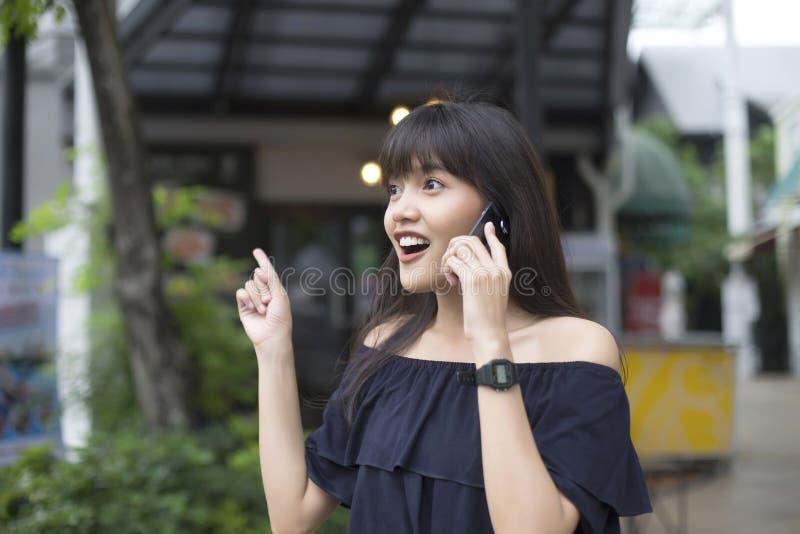 De glimlachende jonge Aziatische vrouw geniet van sprekend smartphone royalty-vrije stock foto's
