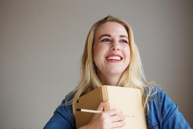 De glimlachende jonge blonde vrouwelijke boeken en het potlood van de studentenholding stock afbeeldingen
