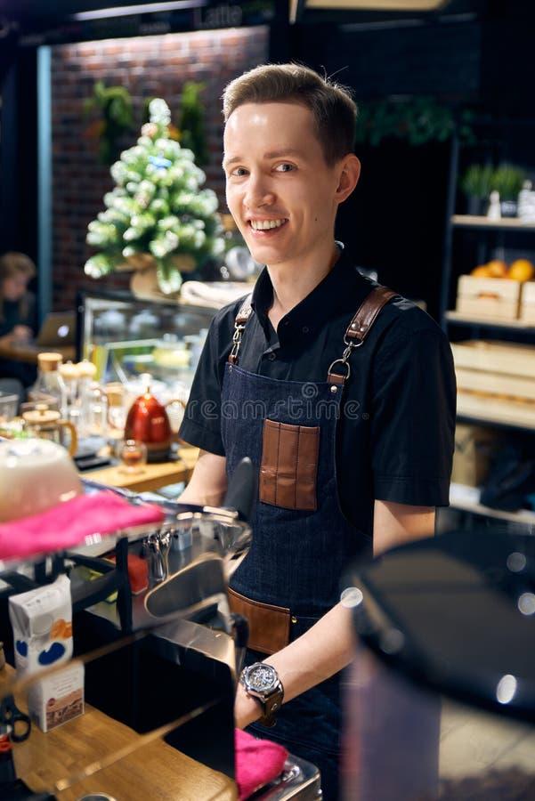 De glimlachende jonge mens achter de bar Barista bereidt koffie voor en glimlacht de comfortabele atmosfeer van de koffiewinkel stock afbeeldingen