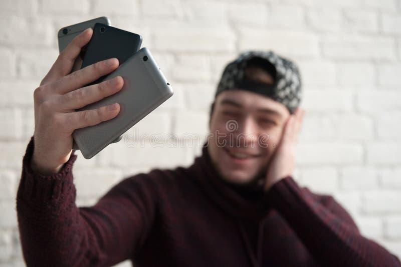 De glimlachende jonge mens bekijkt drie verschillende smartphones die in zijn hand selfie maken stock afbeeldingen