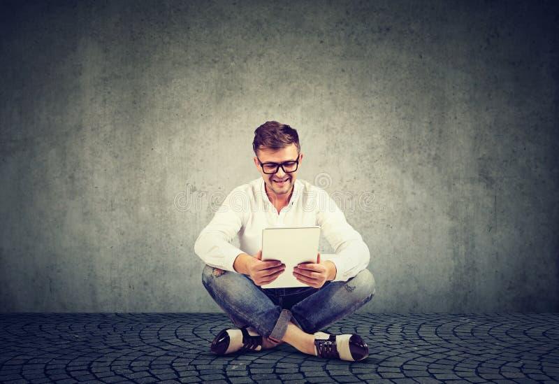 De glimlachende jonge mens in glazen die een tabletzitting gebruiken ontspande op een vloer royalty-vrije stock afbeeldingen