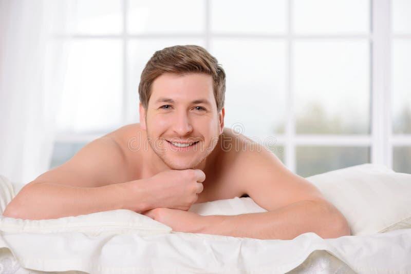 De glimlachende jonge mens legt wakker in bed royalty-vrije stock fotografie