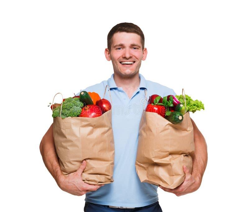 De glimlachende jonge mensenholding die doet hoogtepunt van groenten in zakken winkelen die op witte achtergrond wordt geïsoleerd royalty-vrije stock afbeeldingen