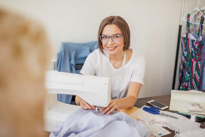 De glimlachende jonge naaistervrouw naait kleren op een naaimachine in haar workshop royalty-vrije stock fotografie