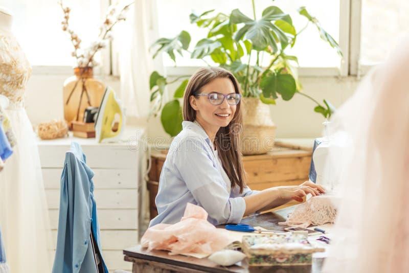 De glimlachende jonge naaistervrouw naait kleren op een naaimachine in haar workshop stock foto