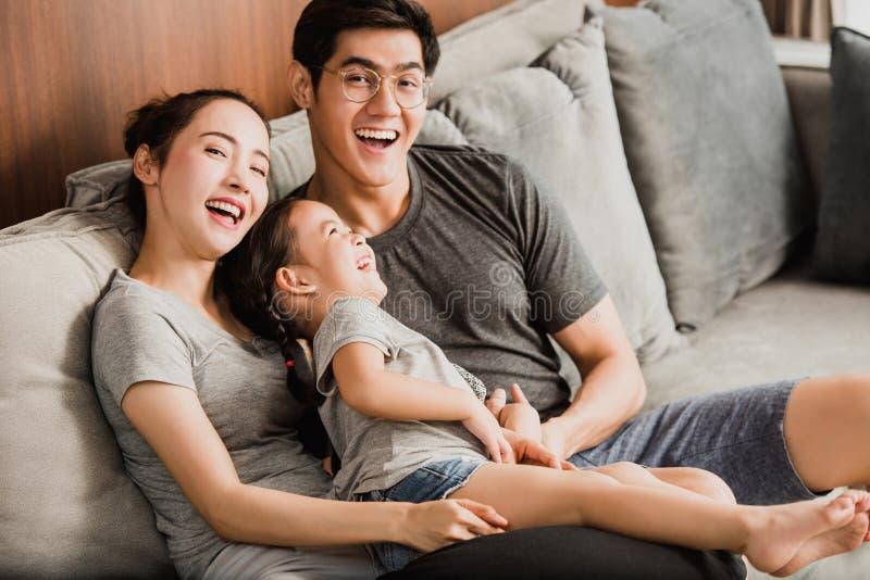 De glimlachende jonge ouders en hun kind zijn zeer gelukkig, zijn zij a stock afbeelding