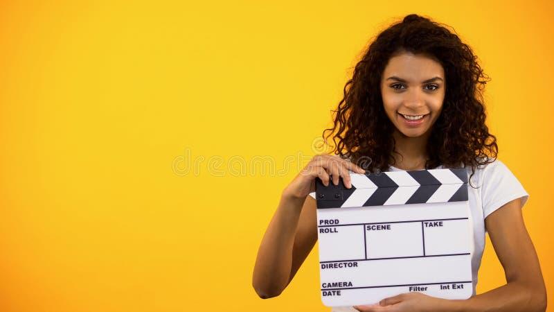 De glimlachende jonge vrouwelijke raad van de holdingsklep op oranje achtergrond, cinematografie stock foto's