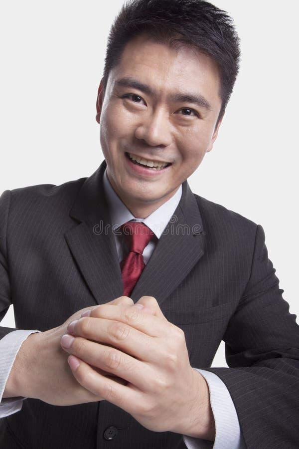De glimlachende jonge zakenman met handen clasped samen het buigen naar camera, studioschot royalty-vrije stock afbeelding