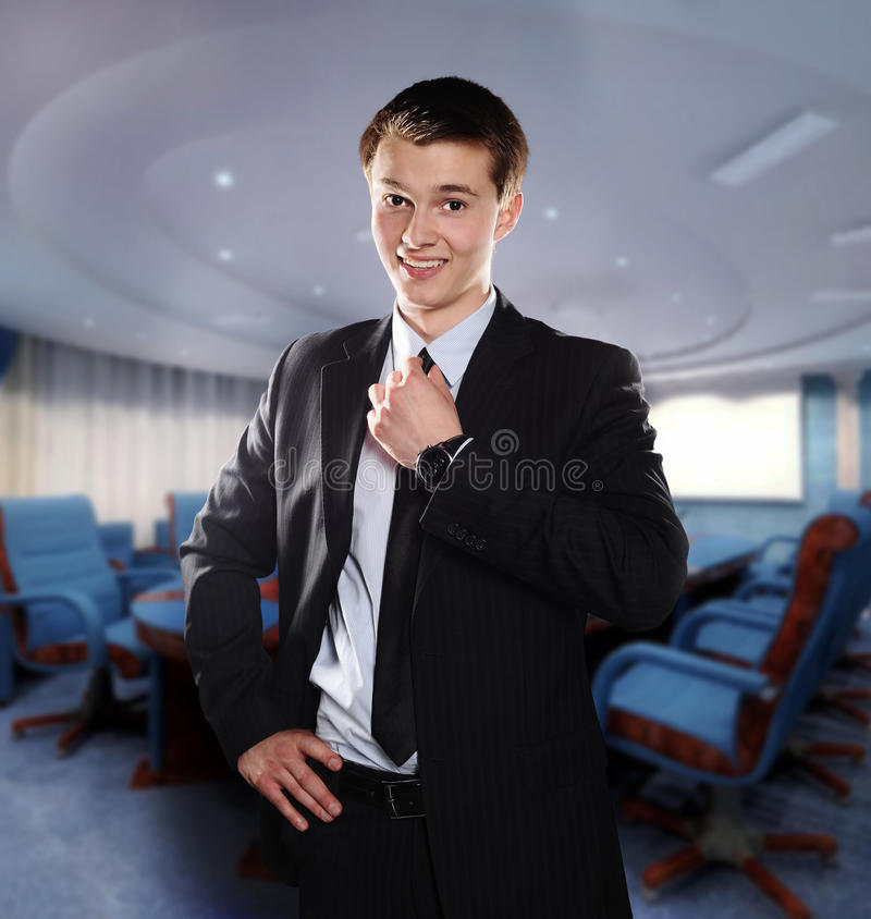 De glimlachende jonge zakenman past zijn band in o aan royalty-vrije stock afbeeldingen