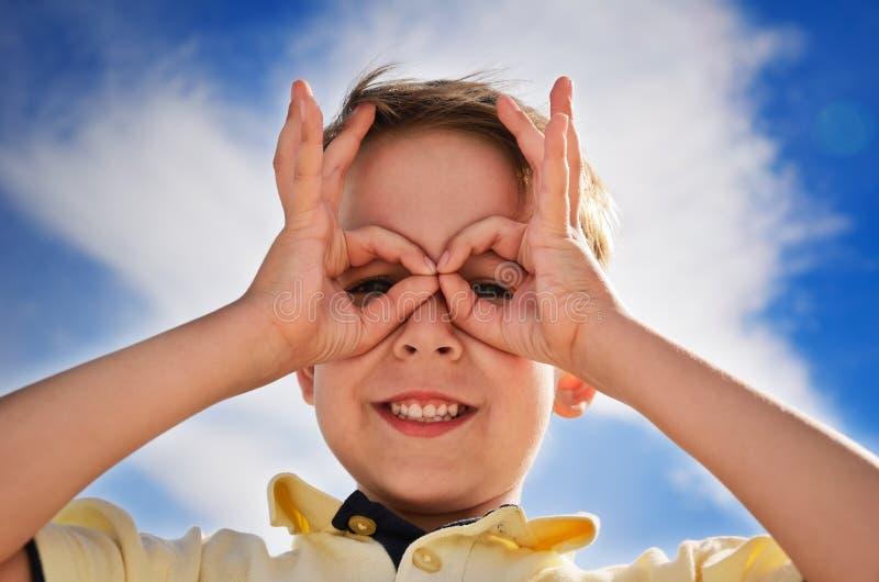 De glimlachende jongen deed vingers zoals verrekijkers en kijkt door hen royalty-vrije stock foto