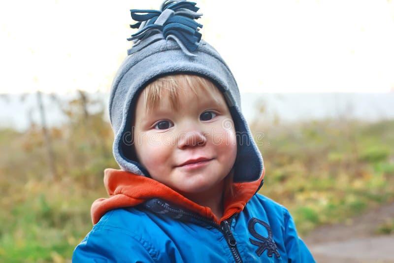 De glimlachende jongen is in een hoed royalty-vrije stock afbeelding