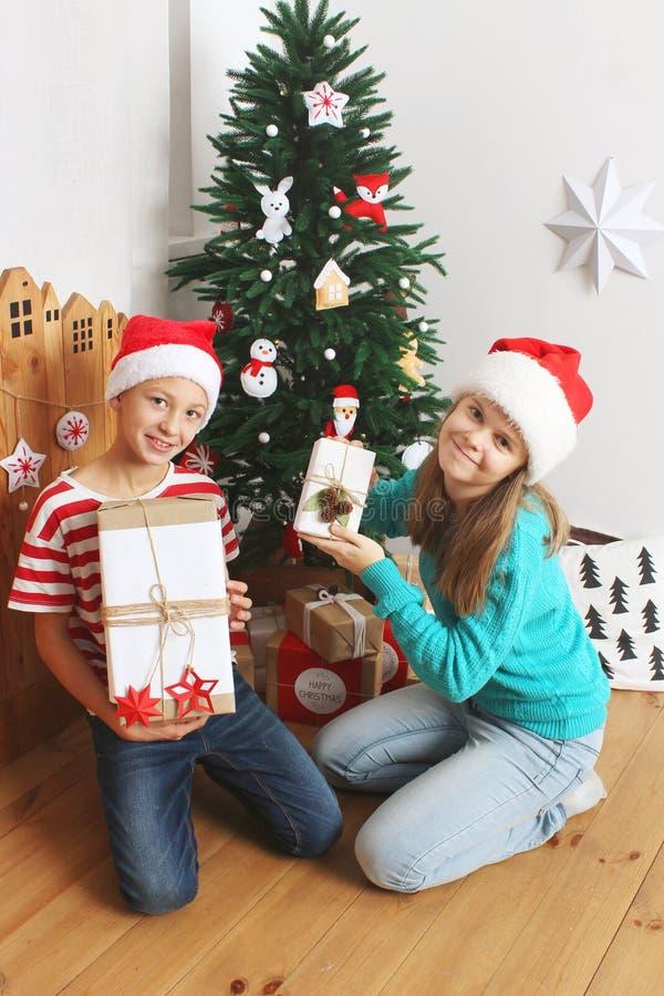 De glimlachende jongen en het meisje met stellen dichtbij Kerstboom voor stock afbeelding