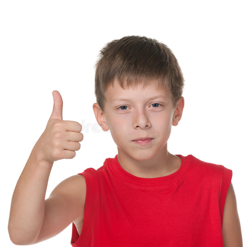 De glimlachende jongen houdt zijn duim tegen stock foto's