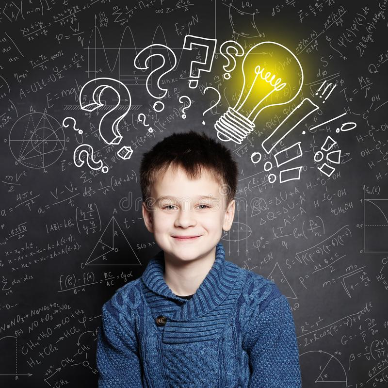 De glimlachende jongen van de Kindschool met lightbulb op achtergrond met formules royalty-vrije stock foto