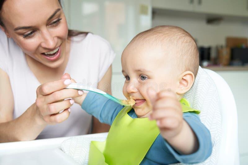 De glimlachende Jongen van de 8 Maand Oude Baby thuis als Hoge Voorzitter die Fed Solid Food By Mother met Lepel zijn royalty-vrije stock foto's