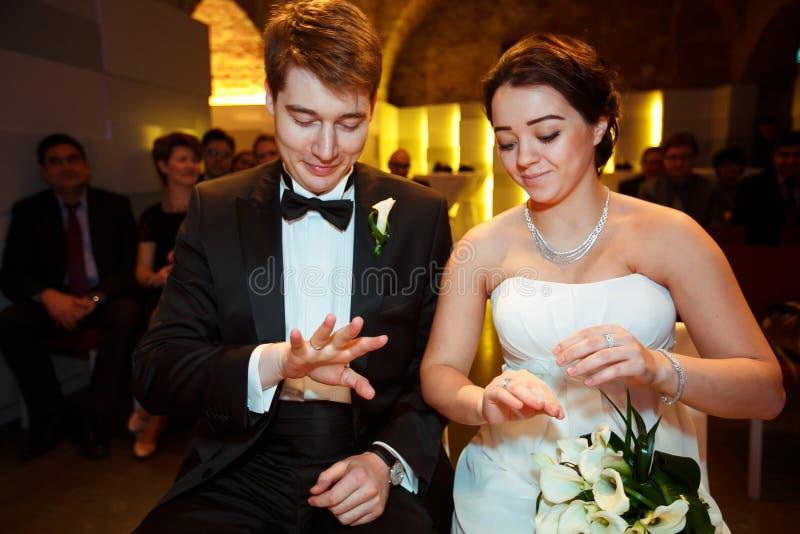 De glimlachende jonggehuwden bekijken hun ringen zittend in het restaurant stock foto