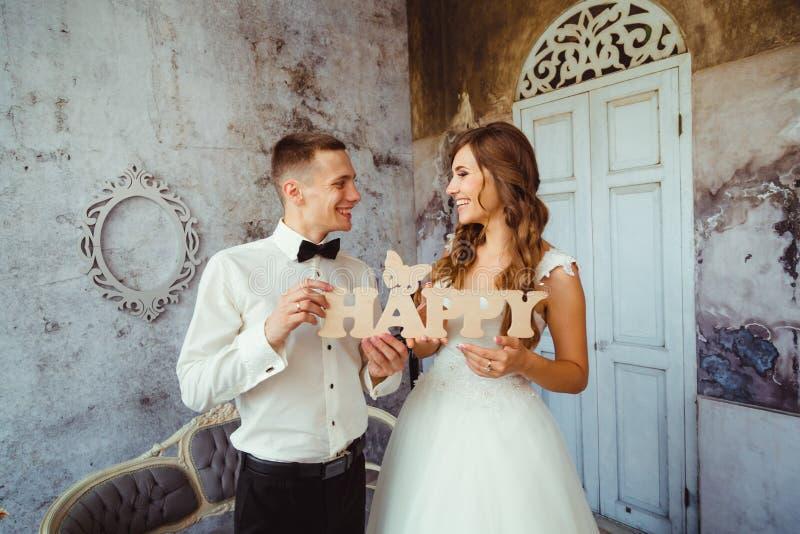 De glimlachende jonggehuwden houden het houten van letters voorzien GELUKKIG stock afbeelding
