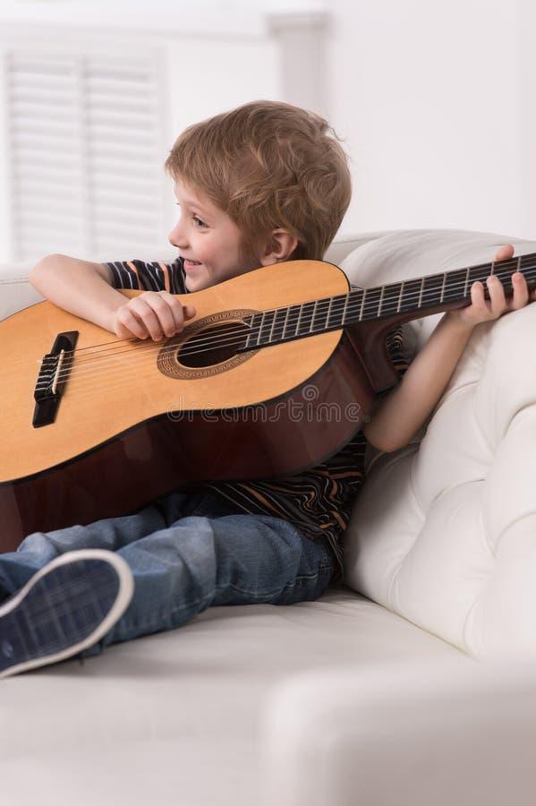 De glimlachende Kaukasische jongen speelt de akoestische gitaar stock foto's